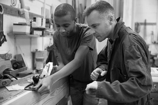 Carpenter with apprentice in woodshop